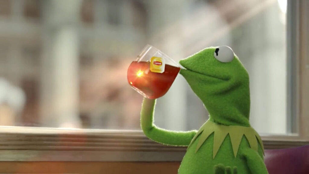 Kermit drinking Lipton Tea by a window with a soft focus background